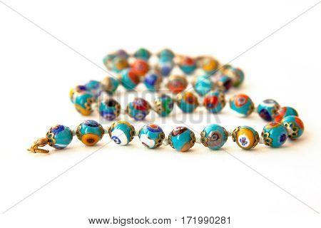 Original Murano glass beads with floral pattern necklace isolated. Venetian traditional colorful millefiori glass jewelry. String of blue beads focus on the first row