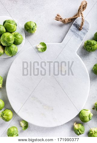 Background with Brussels sprouts and marble cutting board on light gray stone table. Healthy food concept with copy space. Top view.