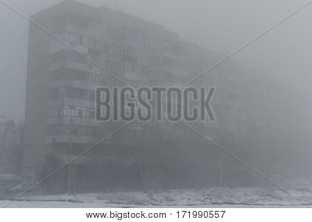 Foggy morning. Multi-storey building in the fog. Snowy morning and fog.