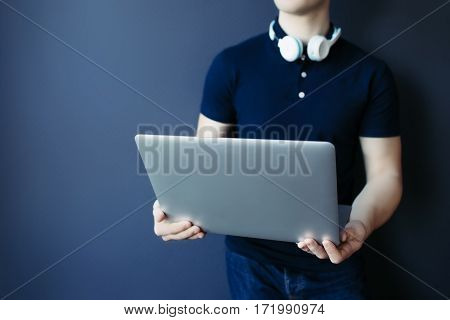 Laptop in young athletic man's hands in t-shirt with headphones. Studuo, unrecognisable.