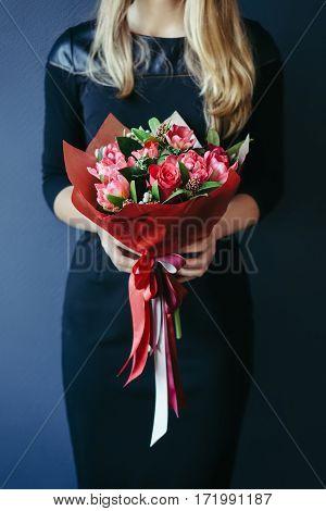 Bouquet of red tulips in girs hands. Studio, unrecognisable