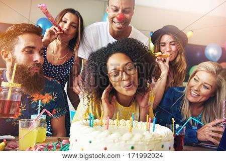 Happy Woman Blowing Candles On Cake