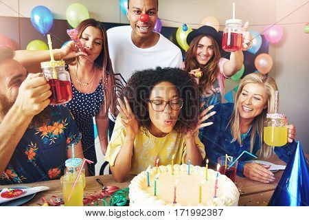 Woman With Eyeglasses Blowing On Cake Candles