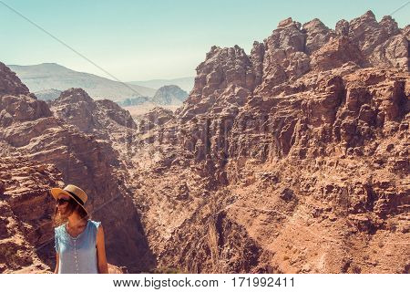 Photo Hipster girl enjoy vacation and journey to Jordan. Gorgeous view from Petra. Negative space for text. Tourism industry. Active lifestyle. Travel concept. Middle East Woman exploring the world