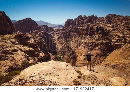 Traveler with raised hand impressed amazing view. Meditation nature. Achievement concept. Ecotourism. Copy space. Rocky mountain landscape. Man enjoy freedom. Summer vacation. Atmospheric background