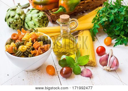 Italian pasta spaghetti fusilli bottle of olive oil basil cherry tomatoes garlic herbs and vegetables dinner ingredients on wood kitchne table