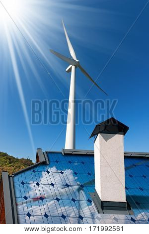 Wind and Solar Energy Concept - Closeup of a house roof with a solar panel and a wind turbine on a blue sky with sun rays