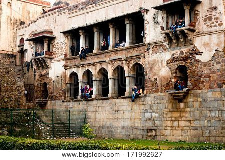 Delhi, India - 22nd Jan 2017: Friends and couples enjoy each others company at the famous hauz khas monument. This is a popular place for lovers to hang out