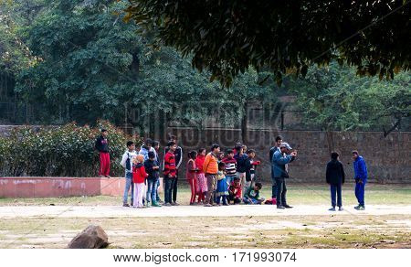 Delhi, India - 22nd Jan 2017: Group of children looking at a street play by other friends while one person video records them