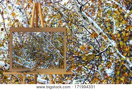 Easel With A Painting Watercolor Illustration Of Winter Landscape In Gloomy Day With Birch Branches