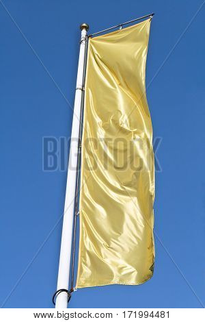 Empty vertical banner golden flag over blue sky