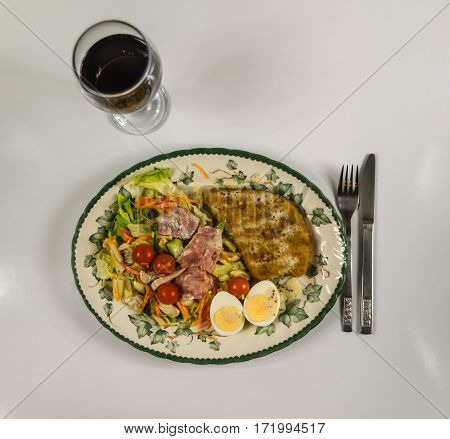 set with chicken bacon cherry tomatoes egg iceberg lettuce and a sauce of red wine in a glass on a decorative plate a delicious lunch