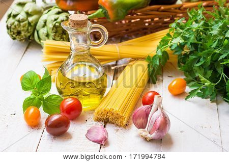 Italian and mediterranean cuisine ingredients spaghetti olive oil garlic tomatoes artichokes sweet pepper in basket on kitchen table outdoors healthy diet