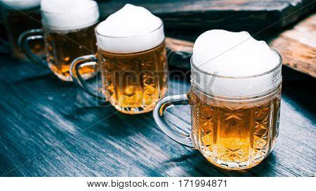 Row of mugs of beer or ale on rustic black wood. Closeup wide view