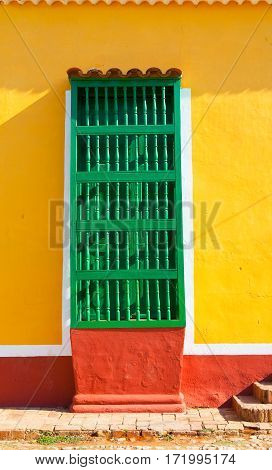 Typical colonial building with green window wooden grate in Trinidad Cuba