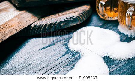 Overflowed mugs of beer or ale on rustic wood. Copy space. Closeup wide view