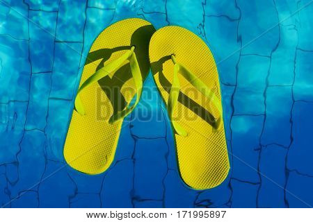 Yellow Flip-flops Floating In A Swimming Pool, A Top View