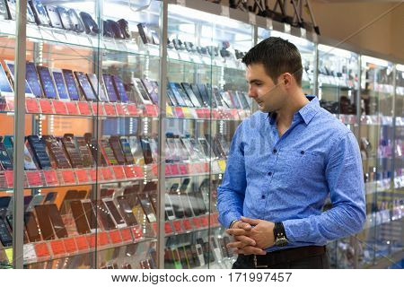 The Young Man, Choosing Camera In The Department Of Household Appliances In The Shopping Center Supe