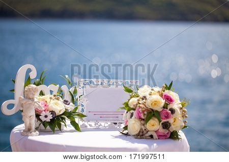 Wedding decoration table with bridal bouquet and letters