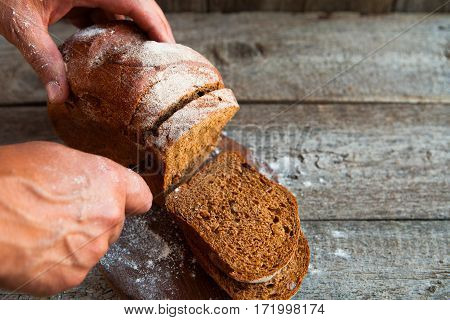 Male Hands Slicing Fresh Home-made Bread On Rustic Table