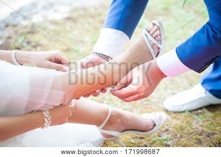 Groom putting on wedding shoes on his bride