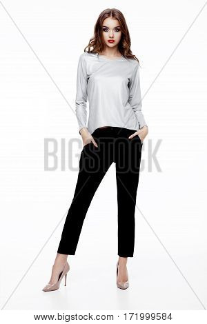 Beautiful fashion model wearing silver top and black pants walking on catwalk on white background