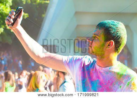 Teenager Taking Photo On Mobile Phone On Holi Color Festival