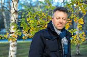 Handsome happy smiling man. Outdoor autumn male portrait. Attractive confident middle-aged man posing in city park, birch grove. poster