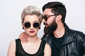 Pretty couple wearing fashion clothes whispering in others ear on white background. Close-up of Bearded man and blond model in sunglasses seducing poster