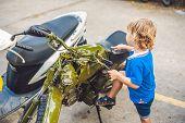 Cute blond boy looking at vintage motorcycle eatables new motorbike. poster