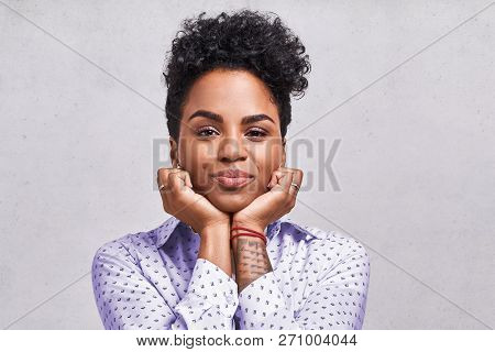 Excited Amazed Beautiful African American Female Looks With Joyful Expression, Keeps Hands Under Chi