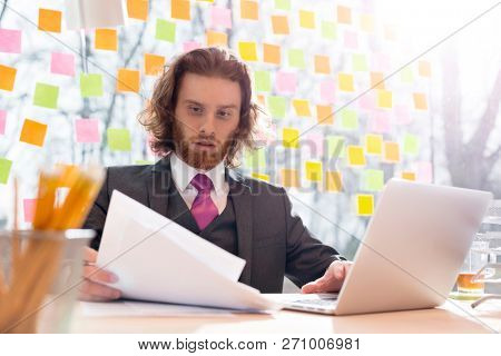 Real life business scenes in the office with a long haired young business man reading paperwork at this desk
