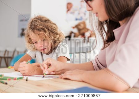 Close-up Of A Child With An Autism Spectrum Disorder And The Therapist By A Table Drawing With Crayo