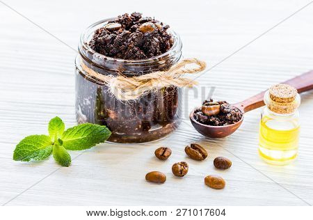 Body Scrub Of Ground Coffee With Oil On White Table Background