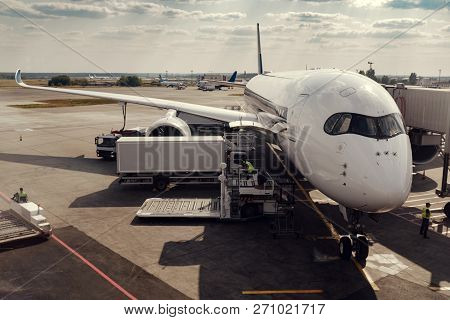 Boarding In Air Plane In Airport. View From Terminal. Refueling And Baggage Loading, Technical Works