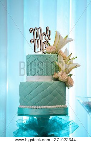 wedding bunk cake, mint color, decorated with mastic and fresh flowers, inscription Mr & Mrs poster