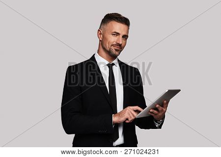 It Professional. Handsome Young Man In Full Suit Using Digital Tablet And Smiling While Standing Aga