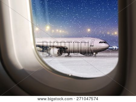 airport and white aircraft at non-flying weather, view through a plane window