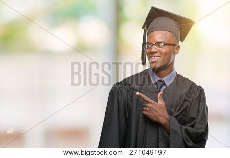 Young graduated african american man over isolated background cheerful with a smile of face pointing with hand and finger up to the side with happy and natural expression on face looking at the camera