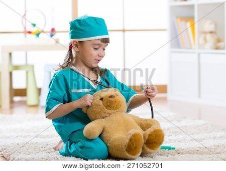 Smiling Kid Girl Playing With Teddy Bear And Pretending She Is A Doctor In Hospital