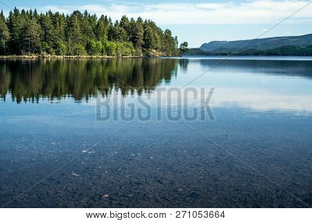A Quiet Peaceful Summer Morning With View Over Crystal Clear Calm Lake With Pebbles In The Bottom An