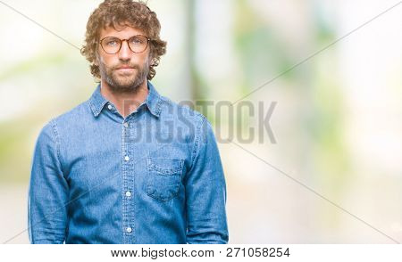 Handsome hispanic model man wearing glasses over isolated background with serious expression on face. Simple and natural looking at the camera.