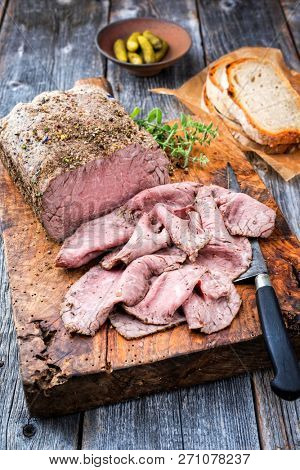 Traditional lunch meat with sliced cold cuts roast beef and farmhouse bread as closeup on a cutting board