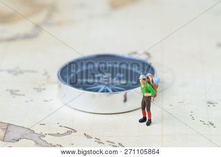 Travel, tourism or wanderlust life concept, plan for next destination, new adventure journey, miniature figure young man backpacker standing with compass on vintage world map. poster