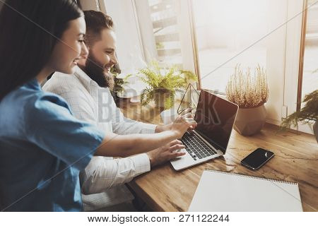 Happy Young Man And Woman Working On Laptop. A Bearded Smiling Man And A Happy Young Girl Are Workin