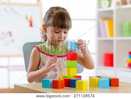 Little Child Girl Plays With Wooden Colorful Cubes Sitting At Table In Nursery Room Or Kindergarten