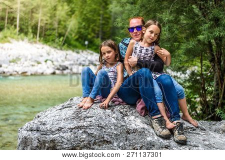 Family Sitting On River Rock After Nature Hiking.
