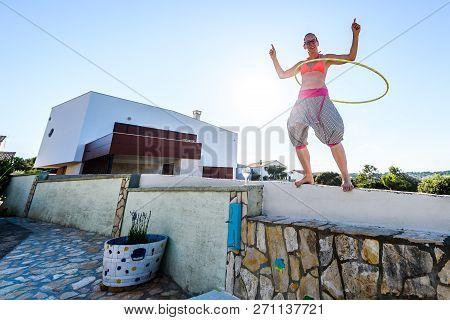 Attractive Adult Woman Is Playing With Hula Hoop In Nature.