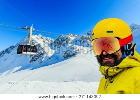 Happy family enjoying winter vacations in mountains . Ski family reflection in goggles mirror.