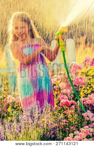 Playful girl watering flowers with rain in the garden at summer day. Child using garden hose on sunny day at sunset lite. Little gardener playing in garden.